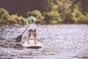 junge beim Stand-Up-Paddling (SUP) in schwimmweste